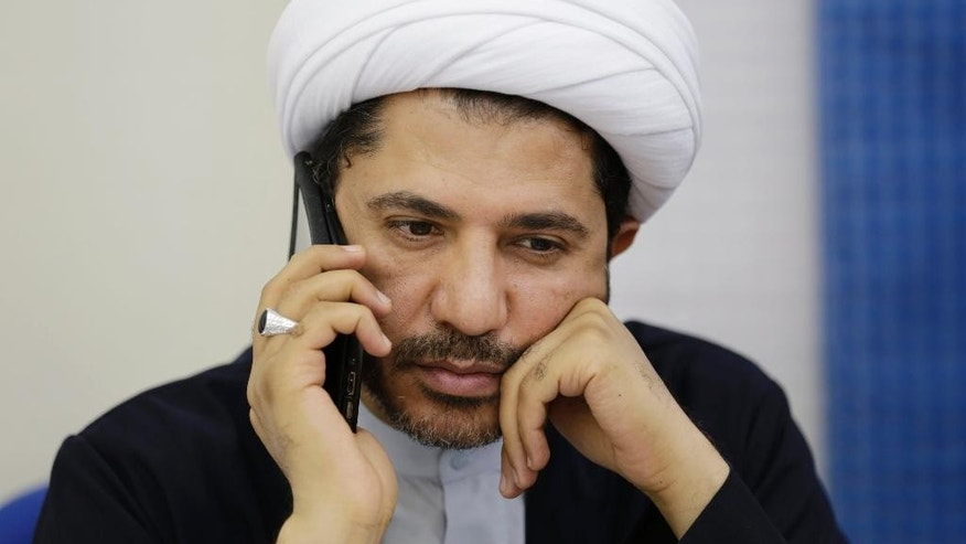 Sheik Ali Salman, leader of the Shiite opposition group Wefaq, speaks on his mobile phone at his party's headquarters in Manama, Bahrain, Tuesday, Oct. 28, 2014. A Bahraini defense lawyer says a court in the Gulf island kingdom has issued an order suspending the activities of the country's main Shiite opposition group less than one month before parliamentary elections are to be held. (AP Photo/Hasan Jamali)