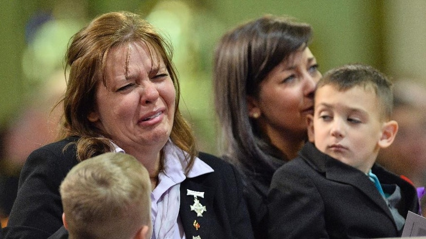Kathy Cirillo cries during the regimental funeral service for her son, Cpl. Nathan Cirillo, as Marcus Cirillo, Nathan Cirillo's son his held by his aunt Natasha Cirillo in Hamilton, Ontario  on Tuesday, Oct. 28, 2014.  Cirillo was standing guard at the National War Memorial in Ottawa last Wednesday when he was killed by a gunman who went on to open fire on Parliament Hill before being shot down in a hail of bullets.  (AP Photo/The Canadian Press, Nathan Denette)