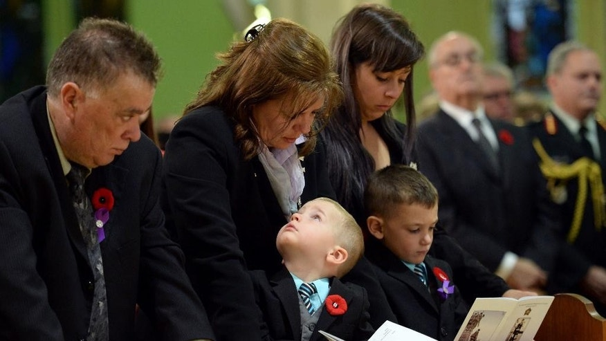 Kathy Cirillo, second from left, and Marcus Cirillo, bottom right, mother and son of Cpl. Nathan Cirillo, attend his funeral in Hamilton, Ontario  on Tuesday, Oct. 28, 2014.  Cirillo was standing guard at the National War Memorial in Ottawa last Wednesday when he was killed by a gunman who went on to open fire on Parliament Hill before being shot down in a hail of bullets.  (AP Photo/The Canadian Press, Nathan Denette)
