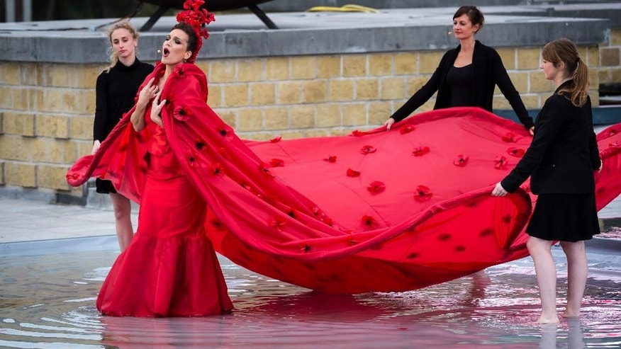 An opera singer wearing a dress with poppies sings during a ceremony at the King Albert I Monument at the Northsea town of Nieuwpoort, Belgium, Tuesday, Oct. 28, 2014. The ceremony commemorates the WWI 100th anniversary of the First Battle of Ypres, focusing on the themes of the refusal to surrender and the flooding of the Yser plain. (AP Photo/Geert Vanden Wijngaert)