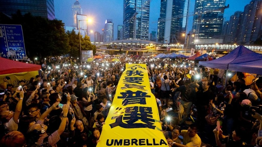 "Oct. 28, 2014: Pro-democracy protesters spread a yellow banner with the words reading: ""I want genuine universal suffrage"" at a rally in the occupied areas outside government headquarters in Hong Kong's Admiralty. (AP)"