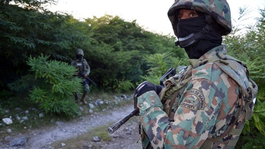 Mexican marines guard the area where new clandestine mass graves were found near the ouskisrts of Cocula, Mexico, Monday Oct. 27, 2014. Mexican authorities searching for 43 missing college students have found human remains in a new area of southern Guerrero state and are testing to see if they belong to the young men who last were seen in police custody a month ago, a government official said Monday. (AP Photo/Alejandrino Gonzalez)