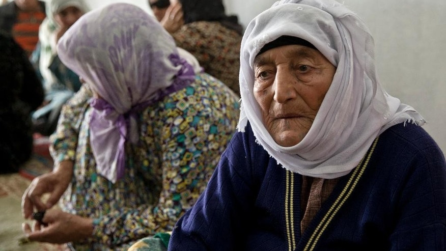 Mahan Kasari, an 87 year-old Syrian Kurdish refugee woman from Kobani sits along with family members in Suruc on the Turkish side of the Turkey Syria border, Monday, Oct. 27, 2014. Kobani, also known as Ayn Arab, and its surrounding areas, has been under assault by extremists of the Islamic State group since mid-September and is being defended by Kurdish fighters. (AP Photo/Vadim Ghirda)
