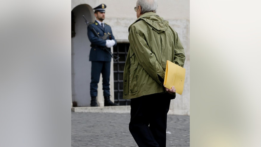 A lawyer holds a folder as he makes his way to the Quirinale Presidential palace in Rome, Tuesday, Oct. 28, 2014. Italy's president will testify in the trial of a former government official accused of negotiating with Mafia bosses to end terror bombings in the 1990s. President Giorgio Napolitano, 89, is to testify behind closed doors Tuesday when the trial moves from Palermo to Rome for the day. Journalists and opposition politicians on Monday demanded that the media, including live TV, be allowed to cover Napolitano's testimony. (AP Photo/Gregorio Borgia)