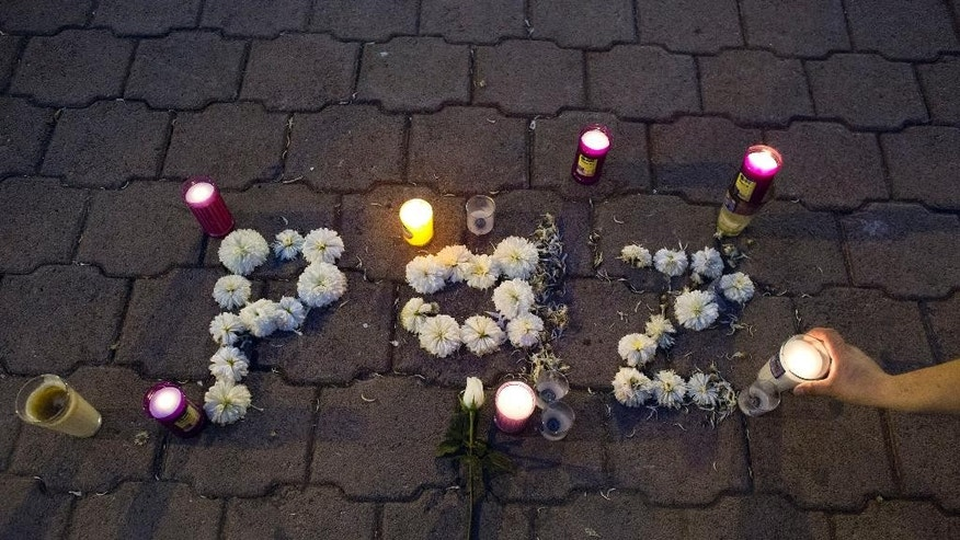 "People place lit candles around flowers spelling out the Spanish word ""Peace,"" on the ground in front of the burnt town hall in Iguala, Mexico, Tuesday, Oct. 28, 2014. Forensic experts combed a gully in southern Mexico on Tuesday for the remains of 43 missing students, as frustration mounted among relatives of both the disappeared and the detained for the lack of answers more than a month into the investigation. (AP Photo/Rebecca Blackwell)"