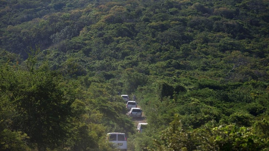 A convoy of vehicles drive towards a site where investigators were searching for human remains, in the densely forested mountains outside Cocula, Mexico, Tuesday, Oct. 28, 2014. Suspects arrested this week told prosecutors that many of the 43 students who disappeared Sept. 26 from Iguala had been held near this location. (AP Photo/Rebecca Blackwell)