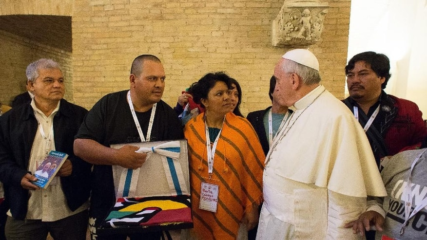 In this photo provided by the Vatican newspaper L'Osservatore Romano, Pope Francis meets with participants of the Global Meeting of Popular Movements, at the Vatican, Monday, Oct. 27, 2014. (AP Photo/L'Osservatore Romano)
