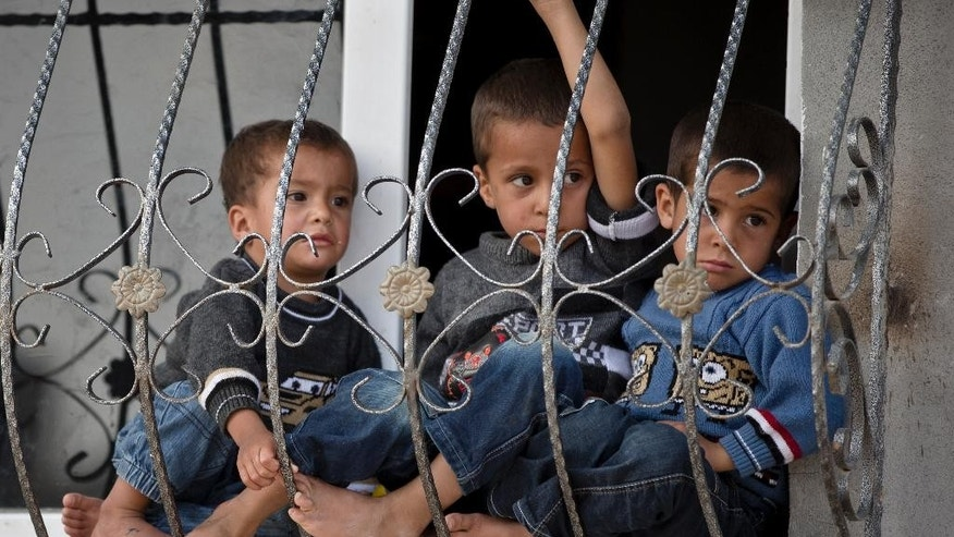 Kurdish children sit at a window in Suruc, on the Turkish side of the border with Syria, across from the Syrian town of Kobani, Monday, Oct. 27, 2014. Kobani, also known as Ayn Arab, and its surrounding areas, has been under assault by extremists of the Islamic State group since mid-September and is being defended by Kurdish fighters. (AP Photo/Vadim Ghirda)