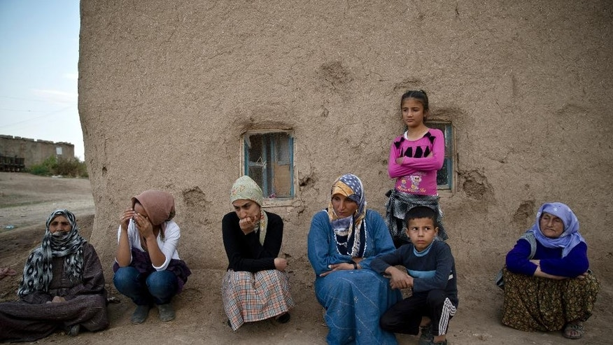 Several members of the same Syrian Kurdish refugee family from Kobani sit in the village of Alanyurt on the Turkish side of the Turkey Syria border, Monday, Oct. 27, 2014. Kobani, also known as Ayn Arab, and its surrounding areas, has been under assault by extremists of the Islamic State group since mid-September and is being defended by Kurdish fighters. (AP Photo/Vadim Ghirda)