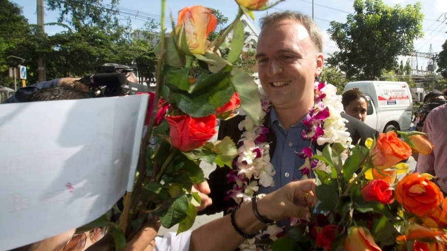 Supporters give flowers to British human rights activist Andy Hall as he arrives at Phra Khanong provincial court for his verdict on criminal and civil defamation cases filed against him, in Bangkok, Thailand Wednesday, Oct. 29, 2014. The Thai court on Wednesday dismissed the first of four criminal and civil defamation cases filed against Hall by a Thai fruit processing company accused of mistreating migrant workers. (AP Photo/Sakchai Lalit)