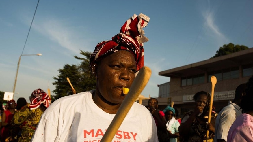 In this photo taken on Monday, Oct. 27, 2014, Woman holding a wooden spoon protest with others during a rally against the longtime president that seeks another term in Ouagadougou, Burkina Faso.  Police used tear gas on Tuesday to disperse an opposition protest in Burkina Faso's capital, as tensions increase ahead of a vote this week on whether the country's longtime president can seek another term. (AP Photo/Theo Renaut)