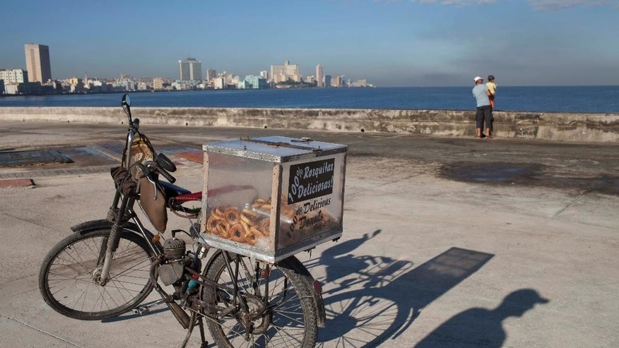 The shadow of self-employed Juan Carlos Lazo is cast on the cement next to his motorized bicycle which he uses to sell donuts along the Malecon in Havana, Cuba, early Tuesday, Oct. 28, 2014. The U.N. General Assembly is expected to vote on Tuesday to condemn the U.S. commercial, economic and financial embargo against Cuba for the 23rd year in a row.  The embargo was first enacted in 1960 following Cuba's nationalization of properties belonging to U.S. citizens and corporations. Sanctions against the Caribbean nation were further strengthened to a near-total embargo in 1962. (AP Photo/Franklin Reyes)