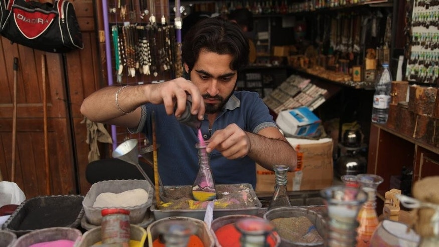Nizar Homsi, 23, places colored sand in a jar in the ancient  bazaar known as the Hamidiyeh souq in downtown Damascus, Syria, Monday, Oct. 27, 2014. His sales have dropped by at least 50 percent since the outbreak of Syria's conflict in 2011. Sales are flagging and prices are rising throughout Syria, a knock-on effect of the rising price of fuel. Traders say they fear ruin as prices are expected to rise even further after the U.S.-bombing of Syrian oil assets controlled by the militant Islamic State group led another hike of fuel prices in October. (AP Photo/Diaa Hadid)
