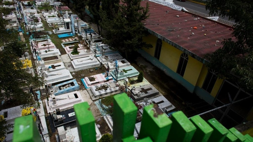 In this Sept. 12, 2014 photo, graves lie tightly packed together in a nearly-full San Isidro cemetery in northern Mexico City. Officials say there is no room available in the capital for new cemeteries. Mexico's capital is rapidly running out of gravesites and many residents of this growing metropolis of 9 million people have to exhume the remains of their loved ones once the burial rights expire to make room for new bodies. (AP Photo/Rebecca Blackwell)