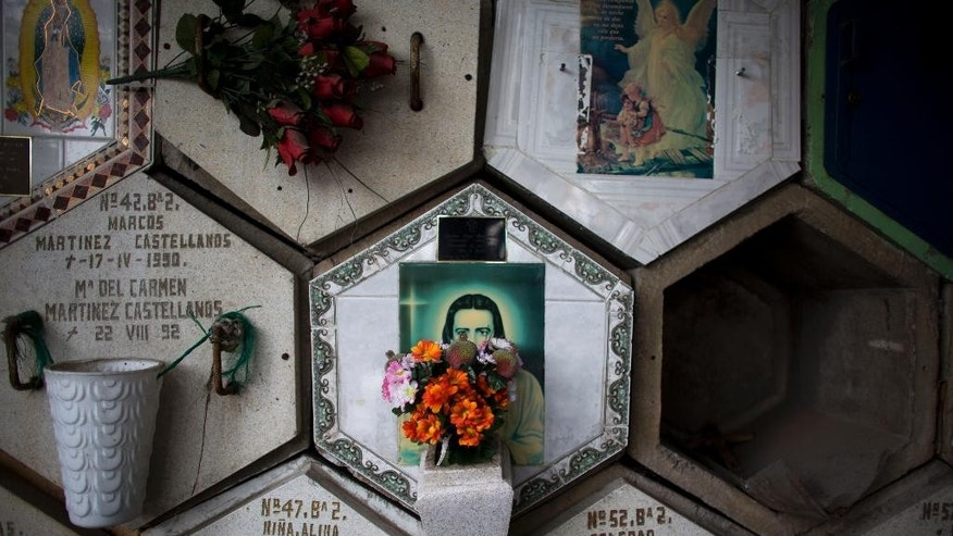 In this Sept. 12, 2014 photo, flowers decorate burial niches at San Isidro cemetery in northern Mexico City. Once exhumed, families put the remains in above-ground niches offered by the cemetery, cremate them, or bury them in a different plot. The lack of cemetery space has prompted the city's legislative assembly to propose a law that would reduce the time a body can remain in a grave and encourage people to cremate the bodies of their love ones. (AP Photo/Rebecca Blackwell)