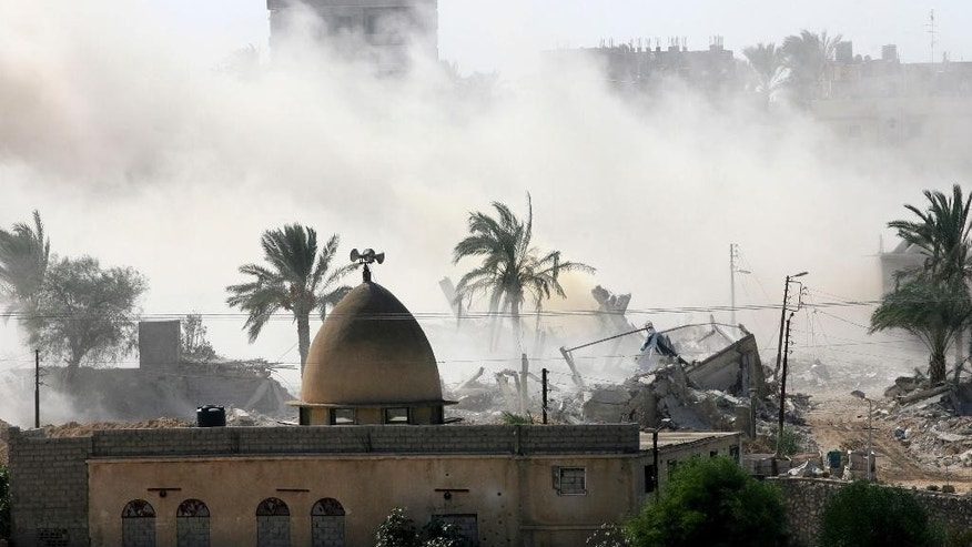 Smoke rises after the Egyptian army demolished houses on the Egyptian side on the border town of Rafah, Wednesday, Oct. 29, 2014. Egyptians are evacuating their homes along the border with Gazaafter militants attacked an army post, killing at least 31 soldiers last week. (AP Photo/Eyad Baba)