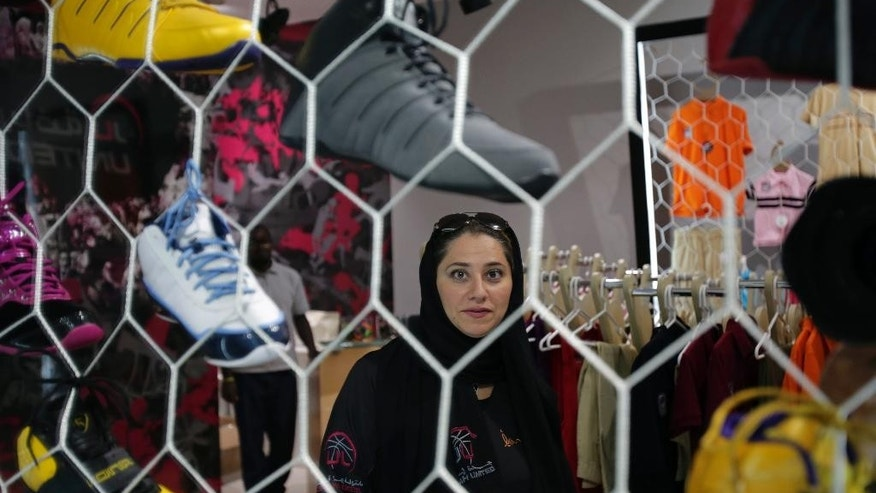In this May 12, 2014 photo, Jiddah United sports club founder Lina Almaeena stands in her sporting goods shop in Jiddah, Saudi Arabia. Women's basketball is gaining in popularity in a kingdom famous for its public restrictions on female movement and activity. For the players, basketball is not merely a sport but an act of defiance in a country where female access to exercise is outright shunned by ultraconservatives. (AP Photo/Hasan Jamali)