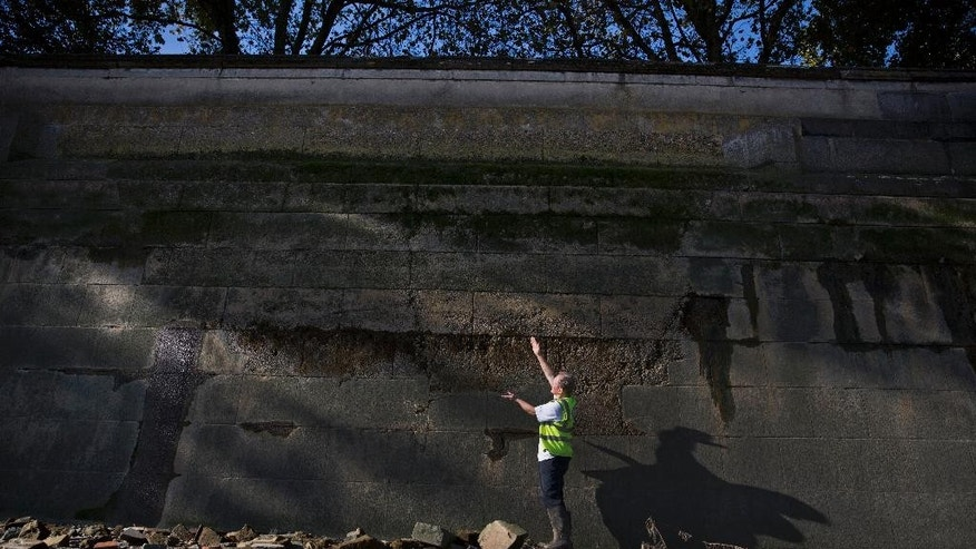 In this Tuesday, Oct. 28, 2014 photo, River Thames archaeology expert Gustav Milne poses for photographs on the foreshore and uses his arms to show the bottom of a repaired section of the embankment river wall that was damaged by a German bomb dropped during World War II in London. Every day, boats full of tourists and commuters pass a pale patch on the wall that lines the River Thames near Britain's Houses of Parliament. Few notice the mark, or recognize it as evidence of how close London came to drowning during World War II. The concrete splotch is a piece of hidden history that has been uncovered by a team of professional and amateur archaeologists. (AP Photo/Matt Dunham)