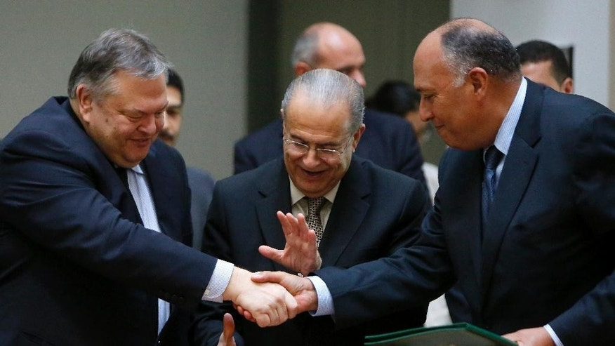 Cyprus' Foreign Minister Ioannis Kasoulides, centre, shakes hands with his counterparts of Egypt Sameh Shoukry, right, and Greek Evangelos Venizelos after their meeting at the foreign ministry in capital Nicosia, Cyprus, Wednesday, Oct. 29, 2014. Venizelos, Kasoulides and Shoukry, told reporters after his meeting with President Anastasiades that Greece will be making its presence more felt in the seas off Cyprus but that it was due to its NATO and U.N. obligations and not because of Turkey's recent activities in the area. (AP Photo/Petros Karadjias)