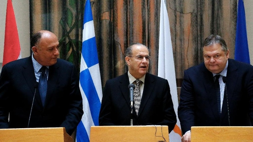 Cyprus' Foreign Minister Ioannis Kasoulides, center, with his counterparts of Egypt Sameh Shoukry, left, and Greek Evangelos Venizelos, right, speak to the media after their meeting at the foreign ministry in capital Nicosia, Cyprus, Wednesday, Oct. 29, 2014. Venizelos, Kasoulides and Shoukry, told reporters after his meeting with President  Anastasiades that Greece will be making its presence more felt in the seas off Cyprus but that it was due to its NATO and U.N. obligations and not because of Turkey's recent activities in the area. (AP Photo/Petros Karadjias)