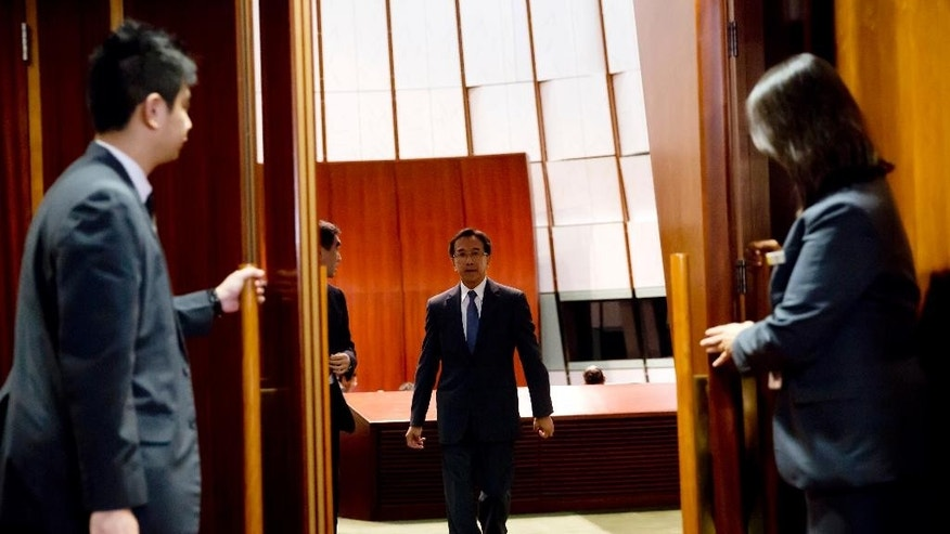 Hong Kong tycoon, chairman of Liberal Party James Tien walks out from Legislative Council chamber in Hong Kong's Admiralty, Wednesday, Oct. 29, 2014. Delegates to China's top government advisory body are expected to vote Wednesday on kicking James Tien out after his comments on the unpopular Hong Kong leader Leung Chun-ying. (AP Photo/Kin Cheung)