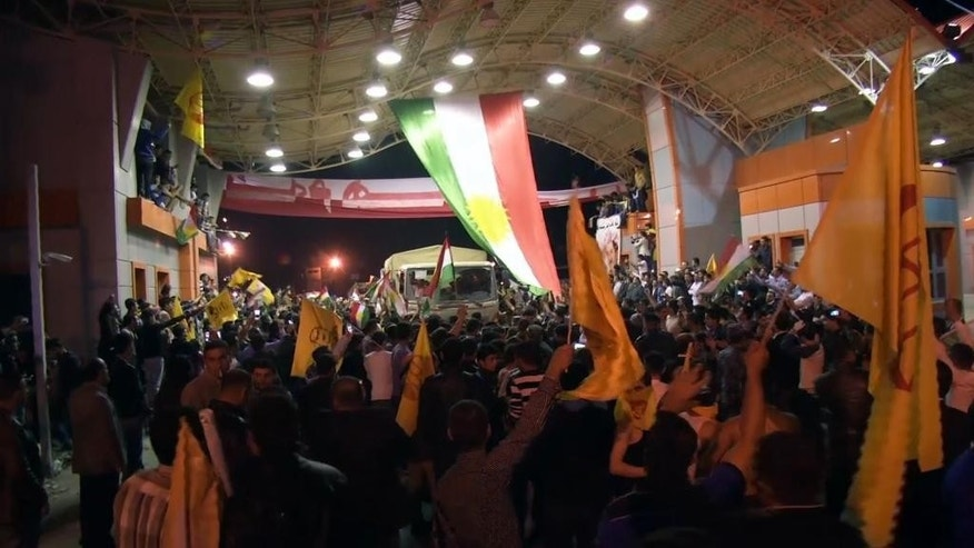In this image taken from video, people welcome peshmerga soldiers as they arrive at the Ibrahim Khalil border entrance in Zakho, Iraq, Wednesday, Oct. 29, 2014. A group of Iraqi Kurdish peshmerga troops crossed the border from northern Iraq into Turkey early Wednesday, headed to Syria to help in the fight against Islamic State militants.  (AP Photo/APTN)