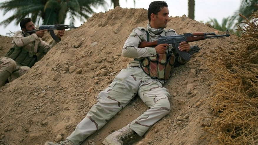 Oct. 27, 2014: In this photo, Iraqi army soldiers aim their weapons on the front line with the Islamic State group in Jurf al-Sakhar, 43 miles south of Baghdad, Iraq.