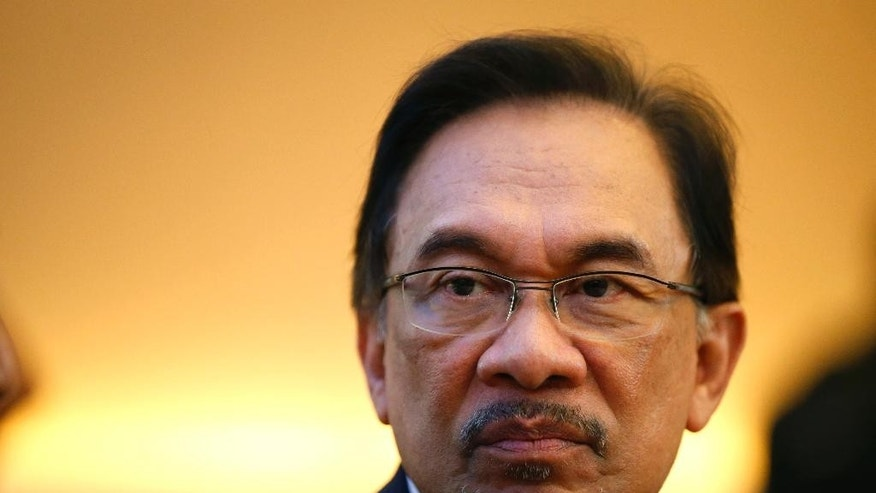 Malaysian opposition leader Anwar Ibrahim glances around during a tea break at the Appeals Court for the second day of his final hearing in Putrajaya, Malaysia, Wednesday, Oct. 29, 2014. The Malaysian top court began hearing a final appeal filed by Anwar against a sodomy conviction widely regarded as a means to neutralize the threat he poses to the country's ruling coalition. Anwar was sentenced to five years in prison in March on charges of sodomizing a male aide in 2008 after Malaysia's appeals court overturned an earlier acquittal. (AP Photo/Vincent Thian)
