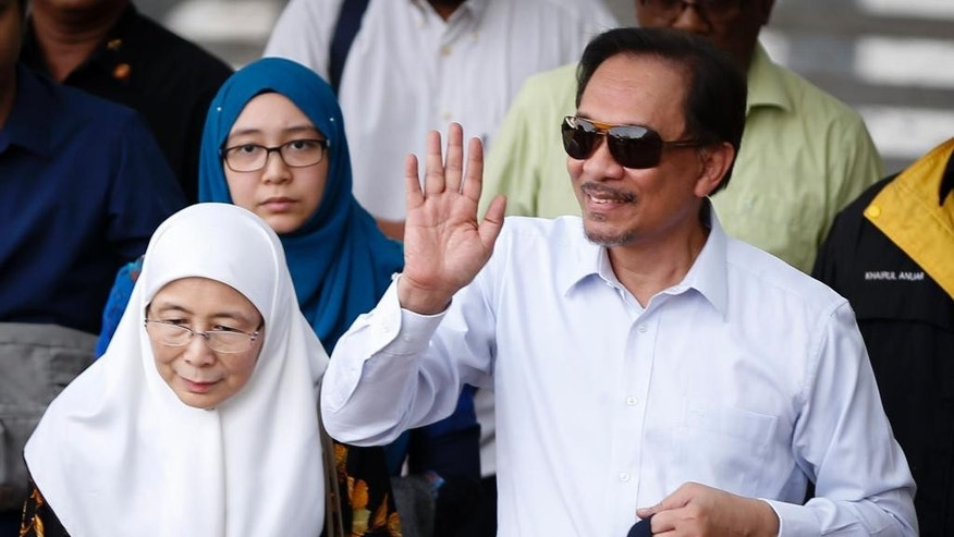 Malaysian opposition leader Anwar Ibrahim walks with his wife Wan Azizah, left, as he arrives at the Federal Court for the second day of his final hearing in Putrajaya, Malaysia, Wednesday, Oct. 29, 2014. The Malaysian top court began hearing a final appeal filed by Anwar against a sodomy conviction widely regarded as a means to neutralize the threat he poses to the country's ruling coalition. Anwar was sentenced to five years in prison in March on charges of sodomizing a male aide in 2008 after Malaysia's appeals court overturned an earlier acquittal. (AP Photo/Vincent Thian)
