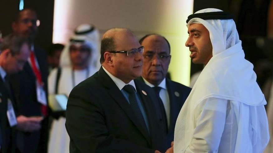 Sheik Abdullah bin Zayed Al Nahyan, UAE foreign minister, right, talks with one of the guests at the opening of Counter-Piracy Conference in Dubai, United Arab Emirates, Wednesday, Oct. 29, 2014. The United Arab Emirates' top diplomat warned Wednesday that the Islamic State group could team up with Islamic militants in Somalia, and he said more should be done to prepare for such a threat. (AP Photo/Kamran Jebreili)