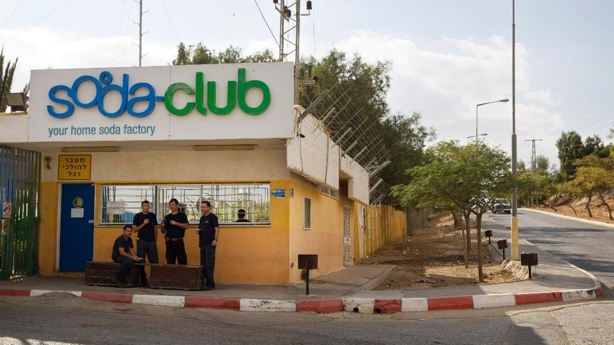 FILE - In this Nov. 22, 2010 file photo, workers stand at the entrance to the Soda Club factory in the Mishor Adumim industrial zone near the Jewish West Bank settlement of Maaleh Adumim. Israeli drink maker SodaStream International Ltd. is to relocate its factory in an Israeli Maaleh Adumim settlement in the West Bank next year to southern Israel, a representative said Wednesday saying the move is strictly for commercial reasons and not due to pressure by pro-Palestinian activists. (AP Photo/Sebastian Scheiner, File)