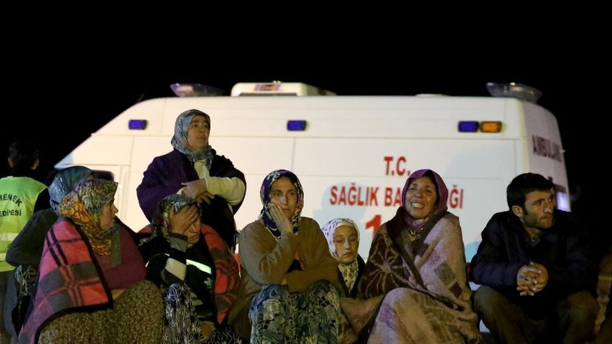 Family members of miners wait as rescue workers use pipes to pump water out of the mine after underground waters flooded a section of the Has Sekerler mine in the town of Ermenek, some 500 kilometers (300 miles) south of Ankara, close to Turkey's Mediterranean coast, early Wednesday, Oct. 29, 2014. Surging water trapped at least 18 workers Tuesday in the coal mine, officials and reports said - an event likely to raise even more concerns about the nation's poor workplace safety standards. Initial reports said flooding inside the coal mine near caused a cave-in, but subsequent reports workers were trapped by the water. (AP Photo/Depo Photos)