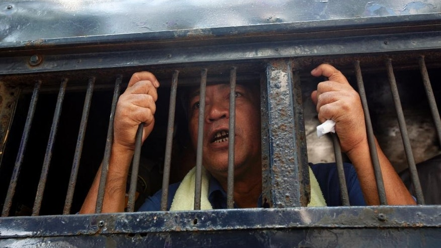 In this May 6, 2014 photo, activist Win Cho talks from a police truck upon arrival for his trial at a township court in Yangon, Myanmar. Win Cho is now serving three months for a January rally calling for the release of all remaining political prisoners, constitutional change and the establishment of a farmers' union in the country. Many of the sweeping reforms that marked Myanmar's transition from dictatorship to democracy have stalled. Though more than 1,300 political prisoners have been released, the U.S. State Department says 30 to 40 remain behind bars, and new detentions are reported every month. (AP Photo/Khin Maung Win)