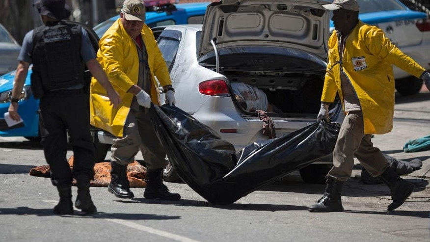 Civil Defense workers carry away a body that was found along with others inside a car in Rio de Janeiro, Brazil, Thursday, Oct. 30, 2014. Police found the bodies of five men, one headless, along with a threatening note inside an abandoned car near the Mangueira slum. (AP Photo/Felipe Dana)