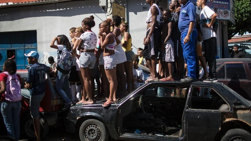 Residents stand on an abandoned car to get a better view as police remove five bodies from a car in Rio de Janeiro, Brazil, Thursday, Oct. 30, 2014. Police found the bodies of five men, one headless, along with a threatening note inside a car abandoned near the Mangueira slum. (AP Photo/Felipe Dana)