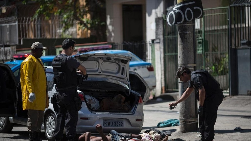 Police take photos of bodies after removing them from inside a car in Rio de Janeiro, Brazil, Thursday, Oct. 30, 2014. Police found the bodies of five men, one headless, along with a threatening note inside an abandoned car near the Mangueira slum. (AP Photo/Felipe Dana)