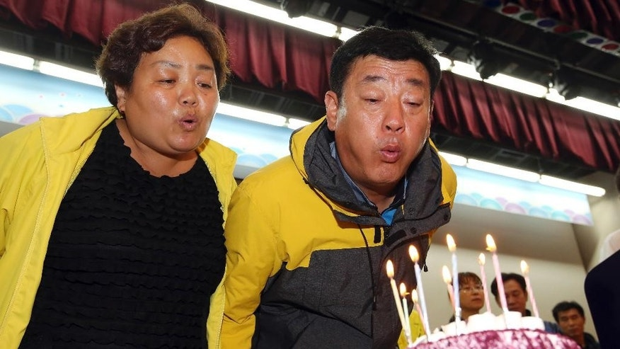 In this Wednesday, Oct. 29, 2014 photo, Hwang In-yeol and his wife Shim Myeong-seop blow out candles on a birthday cake for their daughter Ji-hyeon at a gym on South Korea's southwestern island of Jindo, where they have been staying at since the April 16 sinking of ferry Sewol. They waited seven years to have a child, and then she was born on Oct. 29, 1996. After the ferry disaster that killed her and 303 others, the couple waited again for seven months to see Ji-hyeon's body. The vigil ended Wednesday, Oct. 29 when divers retrieved their only child's body on her 18th birthday. (AP Photo/Yonhap, Park Chul-hong) KOREA OUT