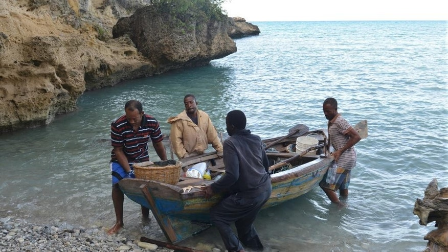 In this Oct. 25, 2014 photo, a group of fishermen pull a wooden boat ashore on a rocky beach in the southern village of Cotes-de-Fer, Haiti. Haitian President Michel Martelly's administration is pursuing plans for Haiti's biggest tourism development ever in the poor coastal area and officials are trying to line up investors to help spur an economic revival. As the country enjoys a period of relative tranquility after years of turmoil, Haitian officials say they see tourism as key to economic development. (AP Photo/David McFadden)