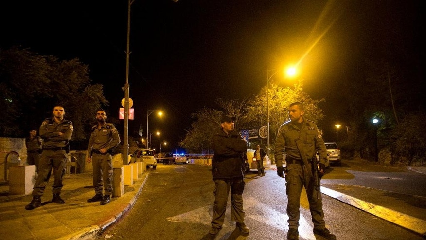 """Israeli police officers stand guard at the scene of a shooting in Jerusalem, Wednesday, Oct. 29, 2014.  Israeli police say a man has been shot in Jerusalem in a suspected assassination attempt. Police spokesman Micky Rosenfeld said the man who was shot Wednesday was a """"relatively known figure"""" and is in serious condition. Police set up roadblocks and were searching for a suspect who had fled on a motorbike. (AP Photo/Sebastian Scheiner)"""
