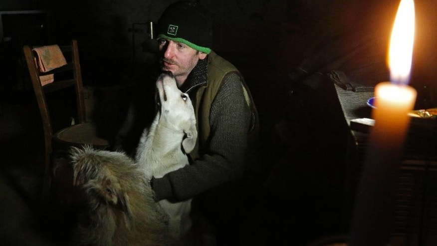 In this photo taken on Monday, Oct. 27, 2014, Vladimir Tumanov, whose home was destroyed in late August, hides from shelling with his dogs in the basement under a hospital not far from Donetsk airport in the town of Donetsk, eastern Ukraine. Donetsk, which has lost about 400,000 of its 1 million pre-war population, is bracing to a winter ahead. In a climate like eastern Ukraine?s, where temperatures typically stay below zero all winter, the damage to the critical infrastructure and lack of effort to provide adequate shelter to people whose homes were destroyed could literally mean a death from the cold. (AP Photo/Dmitry Lovetsky)