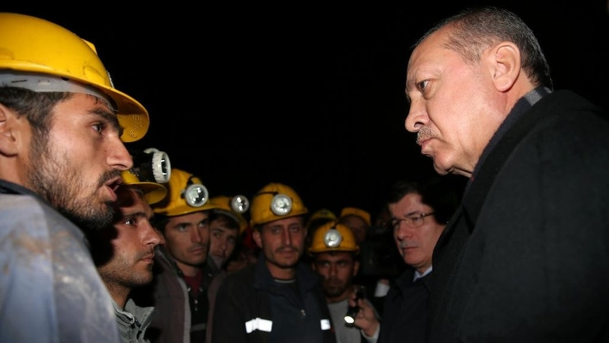 In this photo provided by the Presidential Press Service, Turkey's President Recep Tayyip Erdogan speaks with miners on the second day after underground waters flooded a section of a coal mine in the town of Ermenek, some 500 kilometers (300 miles) south of Ankara, close to Turkey's Mediterranean coast, Wednesday, Oct. 29, 2014. At least 18 workers were trapped inside, officials and reports said _ an event likely to raise even more concerns about the nation's poor workplace safety standards. In May, a fire inside a coal mine in the western town of Soma killed 301 miners in Turkey's worst mining disaster. The fire exposed poor safety standards and superficial government inspections in many of the country's mines.(AP Photo/Kayhan Ozer, Turkish Presidential Press Service, HO)