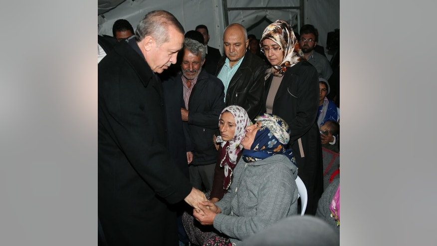 In this photo provided by the Presidential Press Service, Turkey's President Recep Tayyip Erdogan speaks with family members of miners on the second day after underground waters flooded a section of a coal mine in the town of Ermenek, some 500 kilometers (300 miles) south of Ankara, close to Turkey's Mediterranean coast, Wednesday, Oct. 29, 2014. At least 18 workers were trapped inside, officials and reports said _ an event likely to raise even more concerns about the nation's poor workplace safety standards. In May, a fire inside a coal mine in the western town of Soma killed 301 miners in Turkey's worst mining disaster. The fire exposed poor safety standards and superficial government inspections in many of the country's mines. (AP Photo/Kayhan Ozer, Turkish Presidential Press Service, HO)