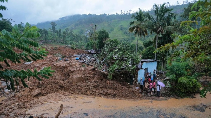 Oct. 29, 2014: Sri Lankan men stand by a damaged house caused by mudslide at the Koslanda tea plantation in Badulla district, about 140 miles east of Colombo. (AP)