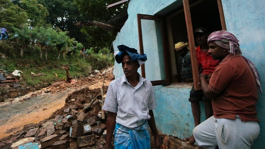 Oct. 29, 2014: Sri Lankan men stand by their damaged house caused by mudslide at the Koslanda tea plantation in Badulla district, about 140 miles east of Colombo. (AP)