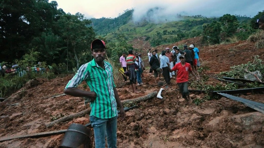 Oct. 29, 2014: Sri Lankan men stand at the site of a mudslide at the Koslanda tea plantation in Badulla district, about 140 miles east of Colombo. (AP)