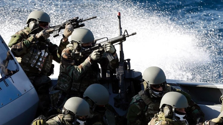 Members of Greek Navy special forces operate during a Greek joint military exercise ''Pyrpolitis'' at the Saronic Gulf, south of Athens on Thursday, Oct. 30, 2014. NATO Secretary General Jens Stoltenberg attended the drill as he is in Athens for talks expected to focus on efforts to counter Islamic State militants in Iraq, the ongoing crisis in Ukraine and renewed tension between Greece and Turkey over oil-and-gas exploration off the coast of divided Cyprus. (AP Photo/Thanassis Stavrakis)