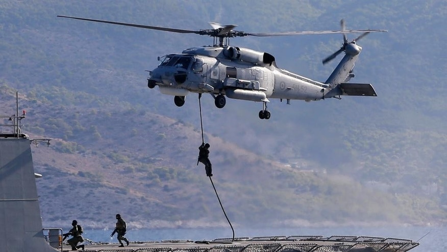 Members of Greek Navy special forces operate from a military helicopter during a Greek joint military exercise ''Pyrpolitis'' at the Saronic Gulf, south of Athens on Thursday, Oct. 30, 2014. NATO Secretary General Jens Stoltenberg attended the drill as he is in Athens for talks expected to focus on efforts to counter Islamic State militants in Iraq, the ongoing crisis in Ukraine and renewed tension between Greece and Turkey over oil-and-gas exploration off the coast of divided Cyprus. (AP Photo/Thanassis Stavrakis)