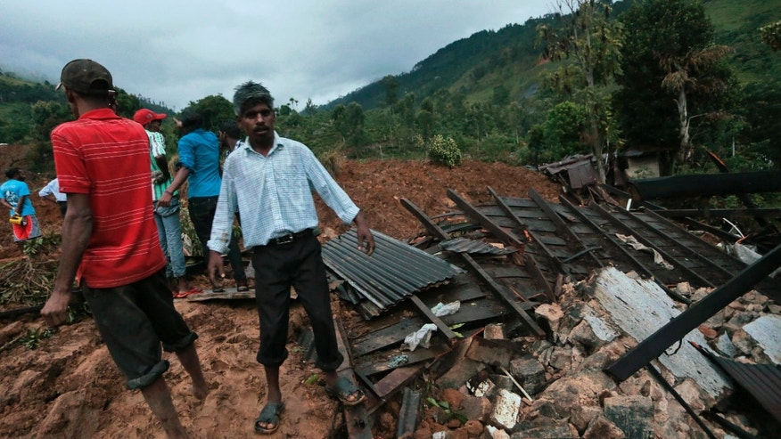 Oct. 29, 2014: Sri Lankans stand at the site of a mudslide at the Koslanda tea plantation in Badulla district,
