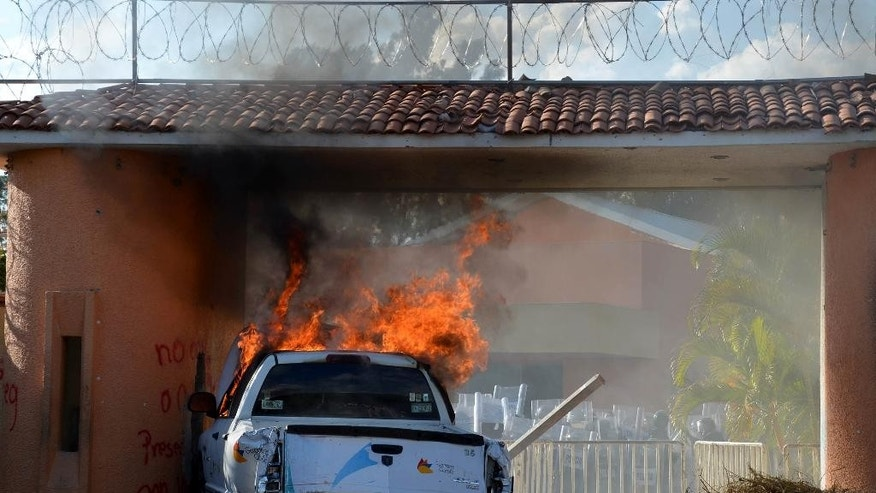 """A vehicle burns after students and teachers attacked the Guerrero State Governor's house, known as """"Casa Guerrero"""", in Chilpancingo, Mexico, Wednesday Oct. 29, 2014. Forensic experts combed a gully in southern Mexico on Tuesday for the remains of 43 missing students, as frustration mounted among relatives of both the disappeared and the detained for the lack of answers more than a month into the investigation. The rural teachers college students disappeared after an attack by police in nearby Iguala. Authorities say it was ordered by former Mayor Jose Luis Abarca and carried out by police working with the Guerreros Unidos cartel. (AP Photo/Alejandrino Gonzalez)"""