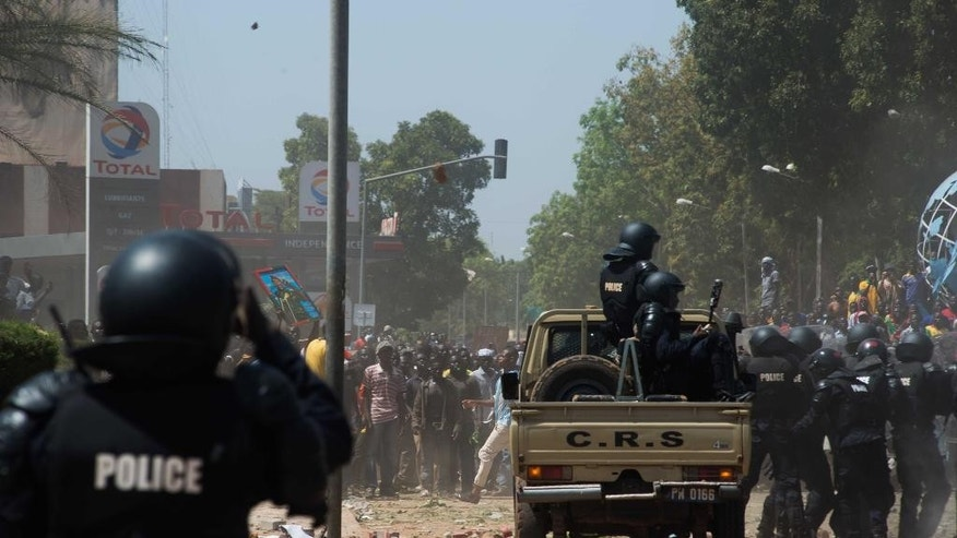 FILE - In this file photo Tuesday, Oct. 28, 2014, Burkina Faso Police clash with protesters as they protest against their longtime president that seeks another term in Ouagadougou, Burkina Faso. Protesters stormed Burkina Faso's parliament Thursday, Oct. 30, 2014,  dragging furniture and computers onto the street and setting the main chamber ablaze, in the most significant challenge to the president's rule during his 27 years in power. (AP Photo/Theo Renaut, File)